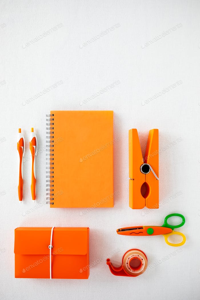 Flat lay of office supplies in orange colour palette.