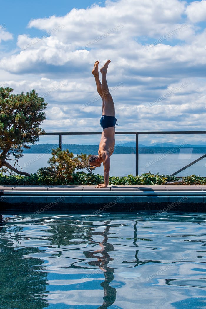 Man doing handstand by swimming pool
