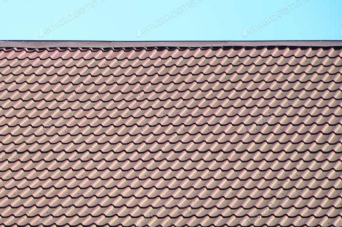 A fragment of a roof from a metal tile of dark red color. Quality Roofing