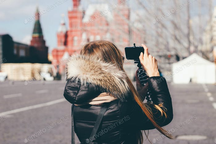 Tourist girl is taking photo on the Red Square in Moscow