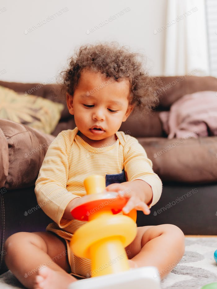 Mixed race curly hair boy at home learning how to stack colorful rings