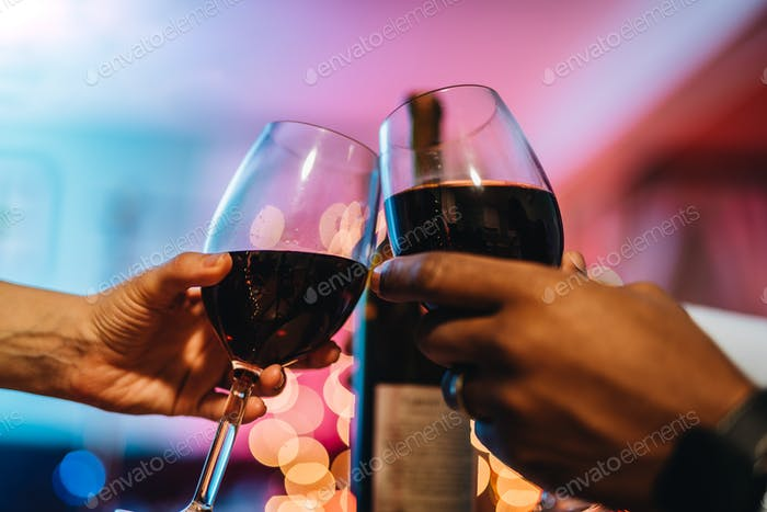 Celebration imagery, black man and white woman celebrating with glass of wine against festive lights