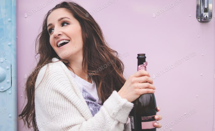 A young woman holding a bottle of pink champagne in front of a pink wall