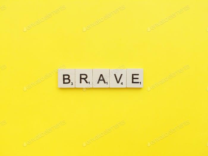 Brave Scrabble Buchstaben Wort auf gelbem Hintergrund