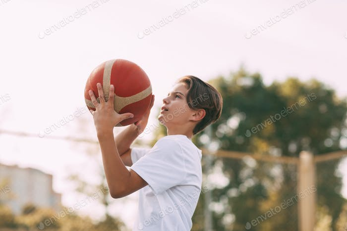 Close-up of a young athlete's hands holding a basketball. The athlete is preparing to throw. Sport,