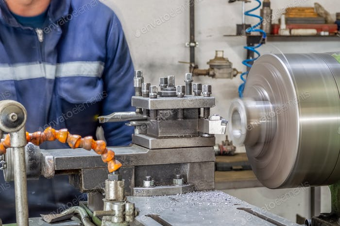 Blue-collar machine operator working with lathe machine in a factory.
