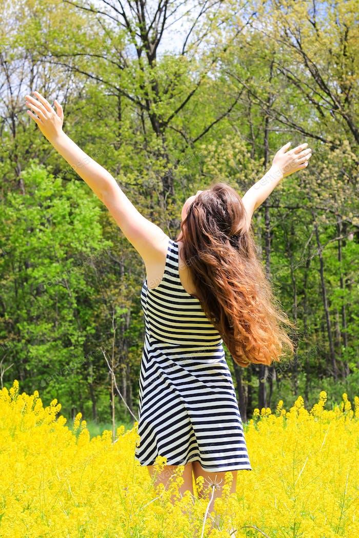 Junge Frau in stilvollem gestreiftem Kleid steht mit ausgestreckten Armen im gelben Rapsblumenfeld