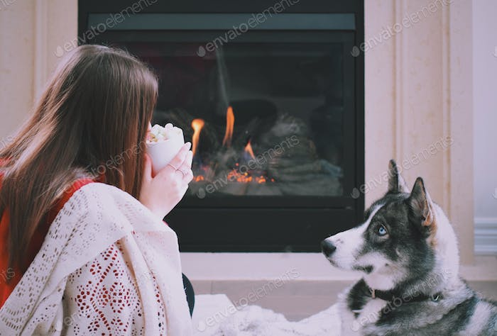 Young girl sitting in front of a fireplace drinking hot chocolate with marshmallows while her dog is