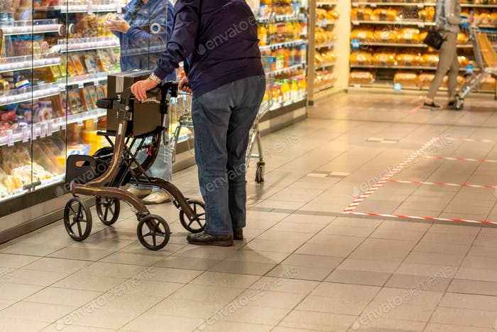 Man, with a wheeled walker or rollator for elderly people, doing groceries during coronavirus