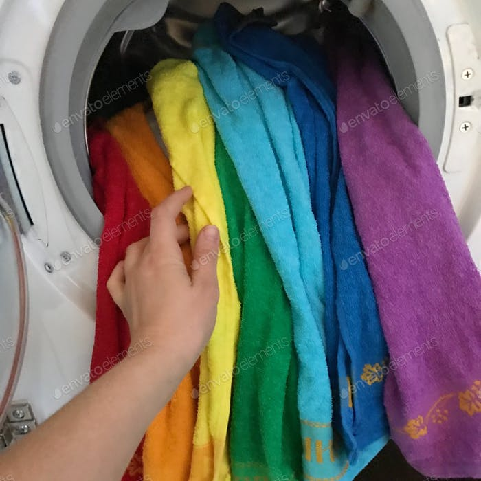 Toallas de color arco iris en lavadora
