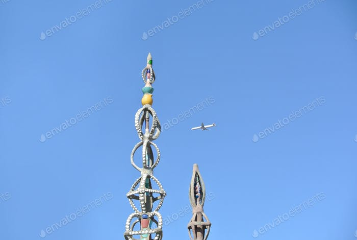 The tops of two of the Watts Towers with an airplane flying by, in the distance.