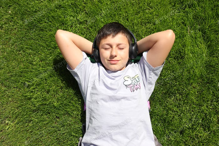 A boy is lying on the grass and listening to music