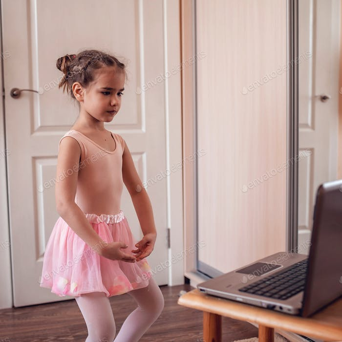 Young ballerina practicing classic choreography during online class in ballet school