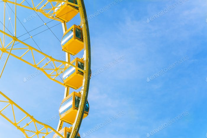 Yellow ferries wheel on blue sky background.