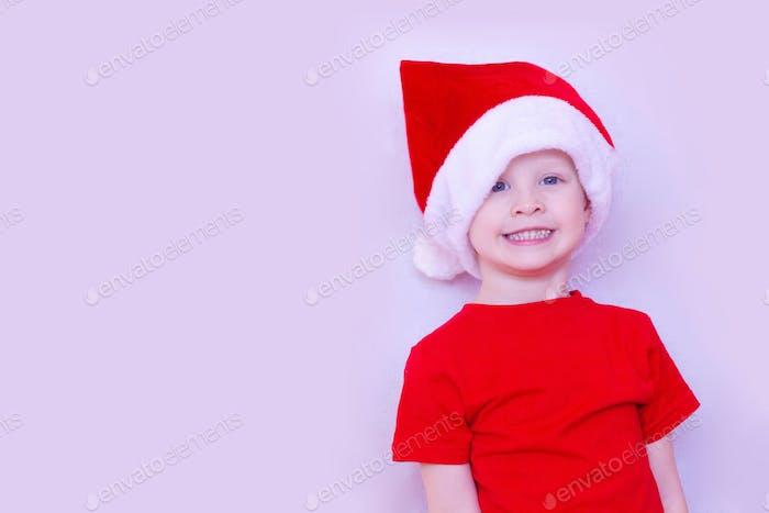 niño con sombrero de santa claus y camiseta roja sonriendo sobre fondo rosa