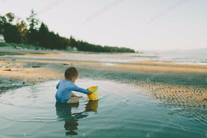 A clothed baby sitting in a tidal pool playing in the evening.