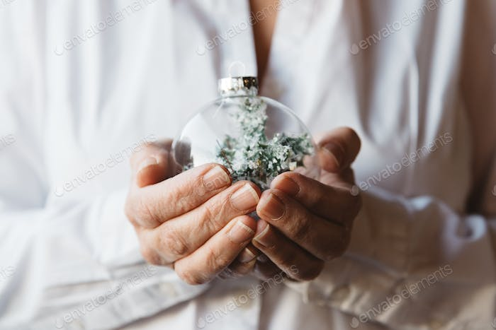 Close-up of woman hands holding Christmas bauble. Focus on foreground