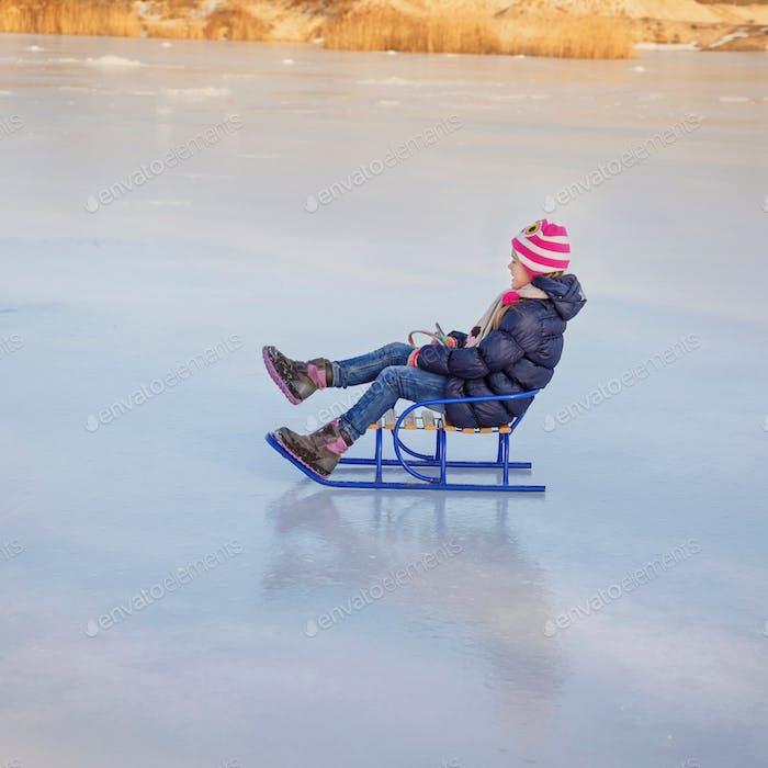 Hübsches kleines Mädchen mit marineblauer Jacke und Strickmütze, die in einem verschneiten Winterpark spielen. Kinder Schlittenschlitten