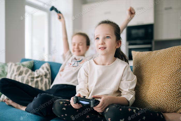 two girls are sitting on a sofa and playing a play station, sisters are playing