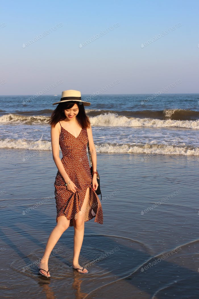 Young woman in a polka dot dress and a straw hat standing on beach