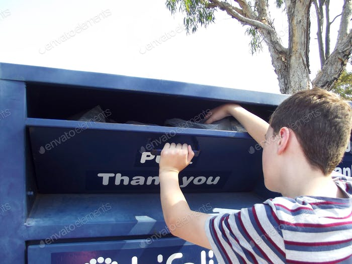 Boy donating clothes to charity in the donation collection bin