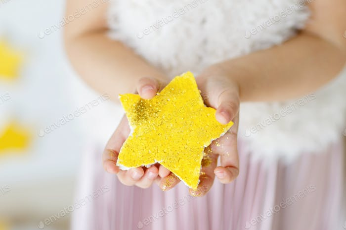 Little girl holding hands yellow star with golden glitter. Trendy color of 2021 year: illuminating