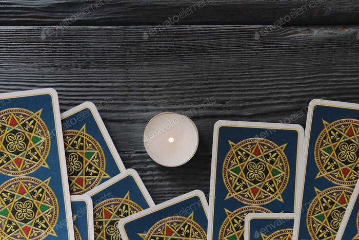 Tarot cards and candle on a wooden table