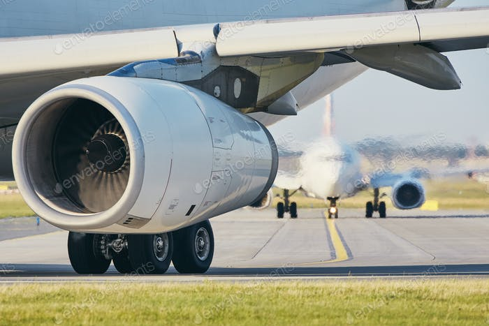 Hot air from jet engine against airplane taxiing to airport runway.