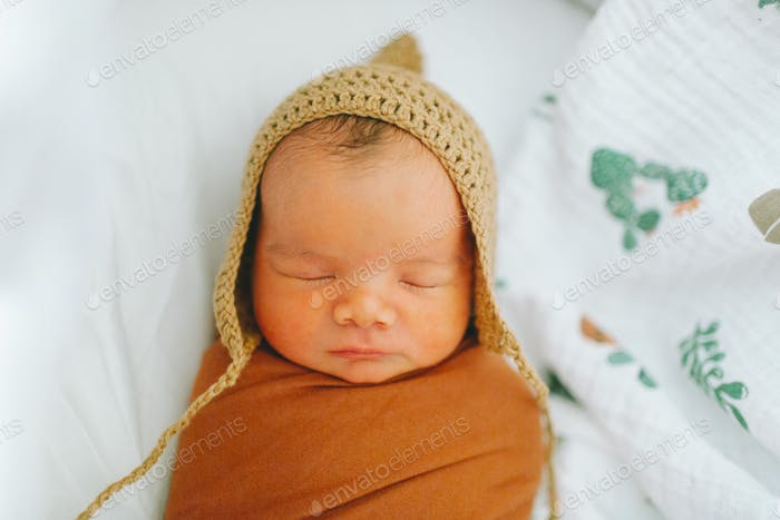 A swaddled newborn baby sleeping in a bonnet.