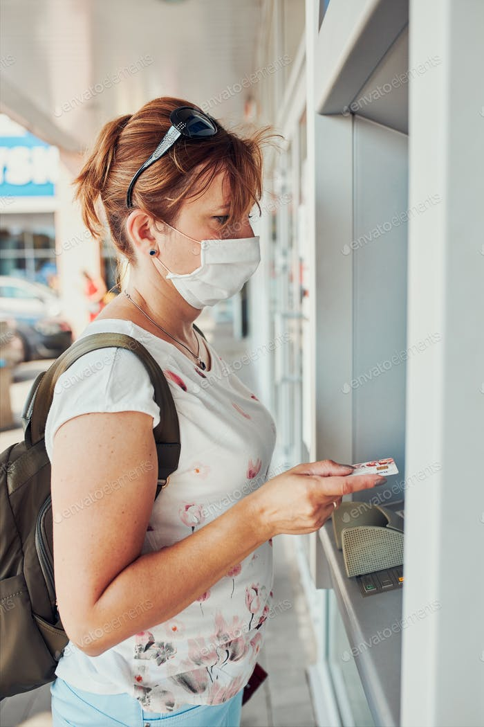 Frau zieht Geld vom Geldautomaten ab, indem sie Debit- oder Kreditkarte im Freien auf der Straße steht