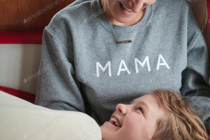 A mother in a 'mama' shirt sharing a laugh with her son on a couch