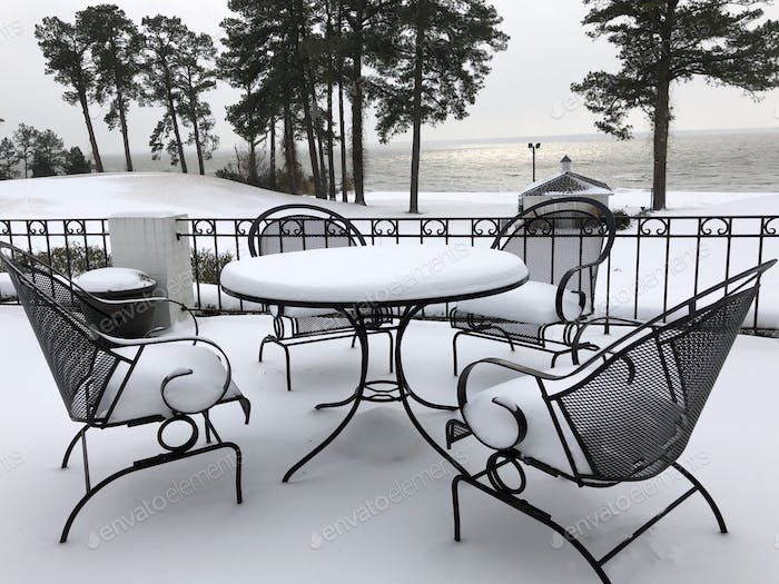 Let it snow. A patio furniture covered by snow and a pretty snowy landscape view of the river