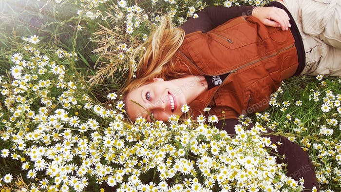 Blonde happy girl lying in a bed of daisies