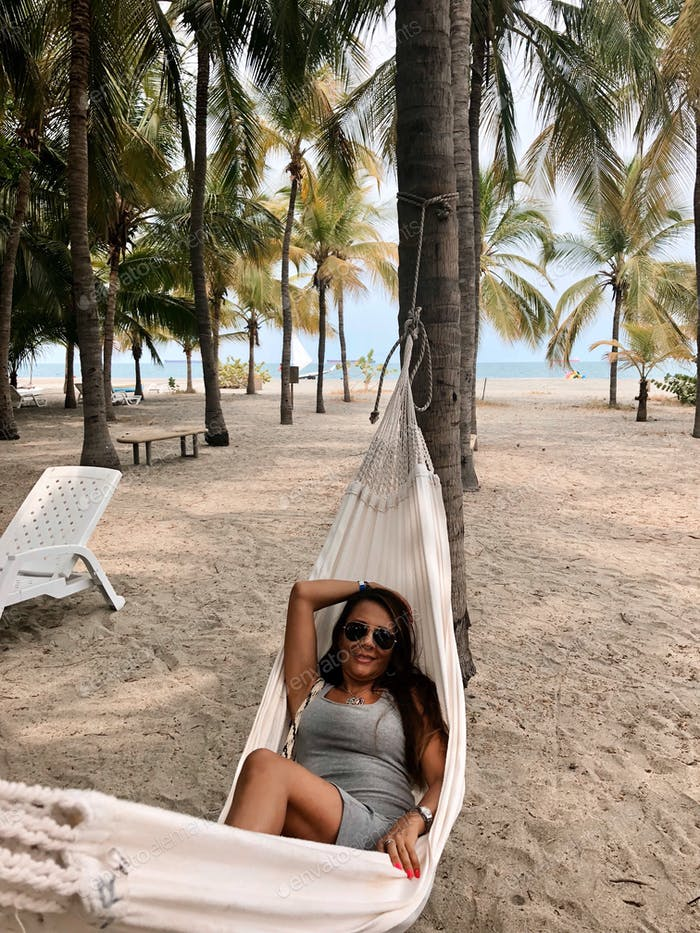 Hispanic Latino young woman resting in a artisanal handmade hammock at a South American beach.