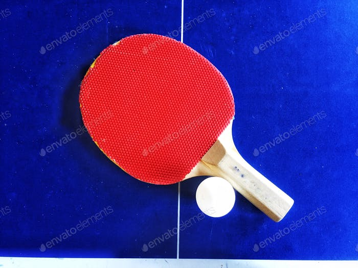 Red table tennis bat and ball on blue ping pong table in a leisure sports background with copy space