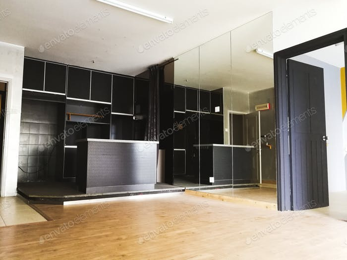 interior of a black kitchen island with glass wall and wooden flooring