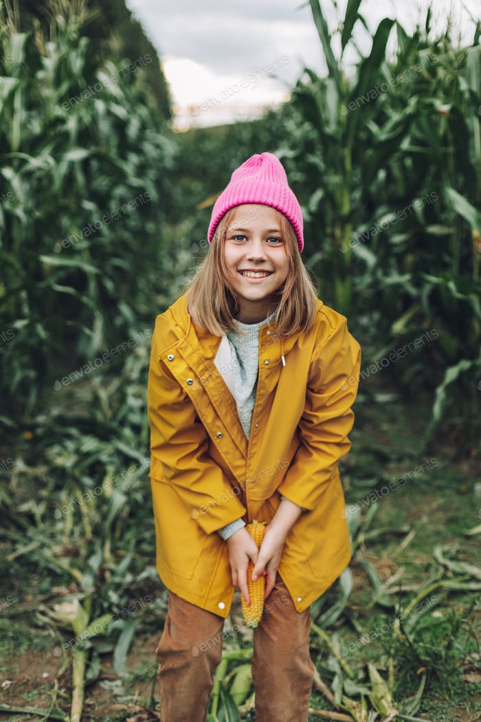Funny little girl dressed in a yellow raincoat and a hot pink cap spoils and bites corn in a cornfie