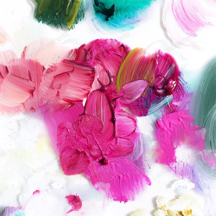 Blick nach unten auf strukturierte Mischung aus rosa Farbfarben auf gebeiztem weißem Künstler Palette Hintergrund.