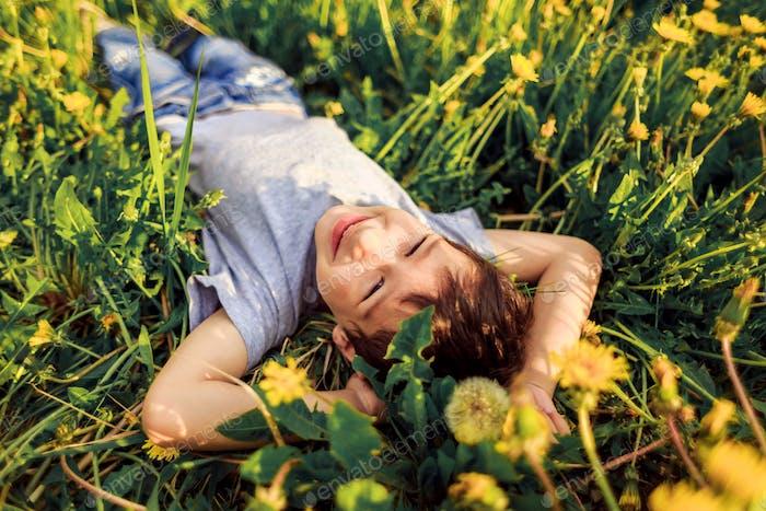 preschooler boy lies in grass in blooming dandelions and smiles