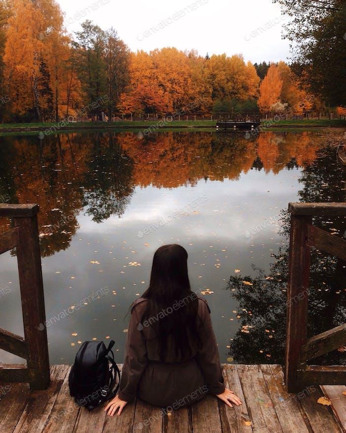 Die  Frau sitzt auf dem Holzsteg in der Nähe des Sees. Herbstliche Atmosphäre