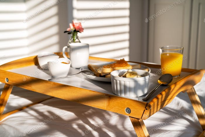 Light and shadows. Breakfast in bed on tray at sunny morning at home - orange juice, coffee, toasts