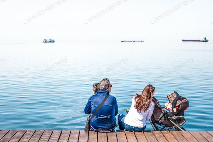 Family Enjoying The View Sitting On The Dock
