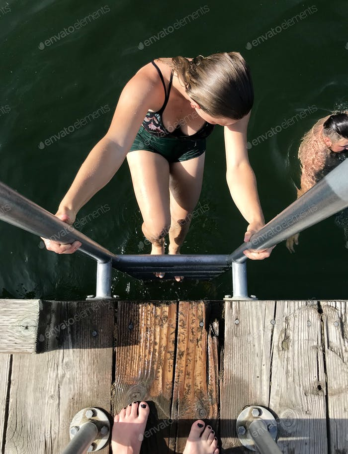 A young woman climbing up a ladder after jumping of a lake dock for a nice swim.