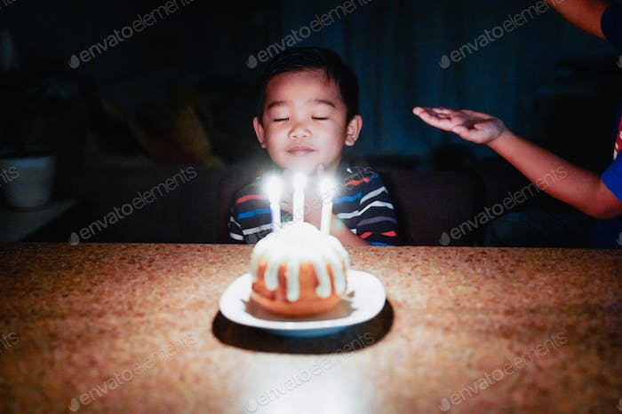 Diverse cute adorable little boy closing eyes blowing out birthday candles.