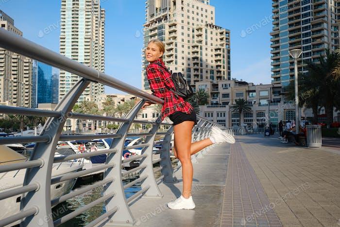 Joven viajera rubia caminando por la calle al aire libre en la ciudad de Dubai