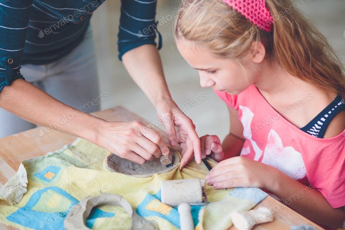 Girl making her first pottery in ceramic workshops