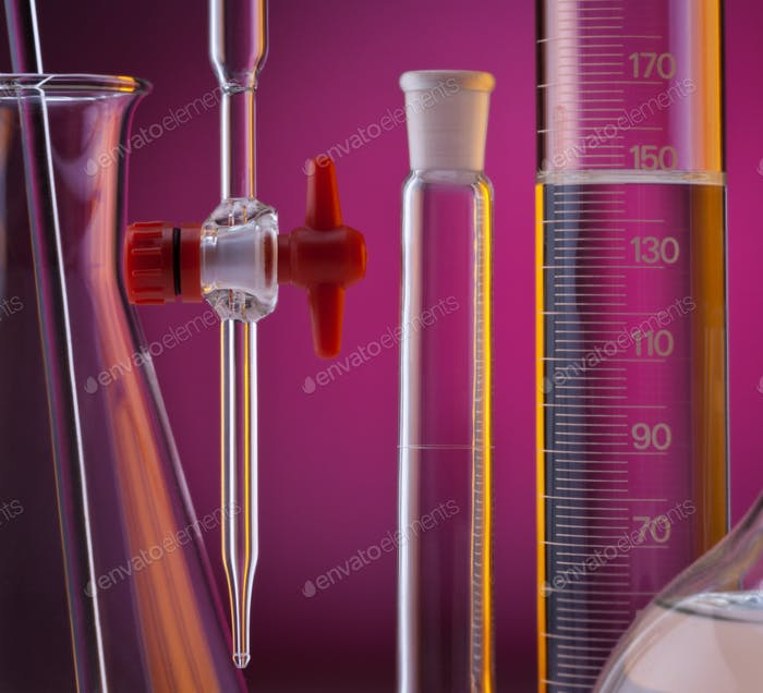 Chemical laboratory glassware - measuring cylinder, pipette, volumetric flask and conical flask.