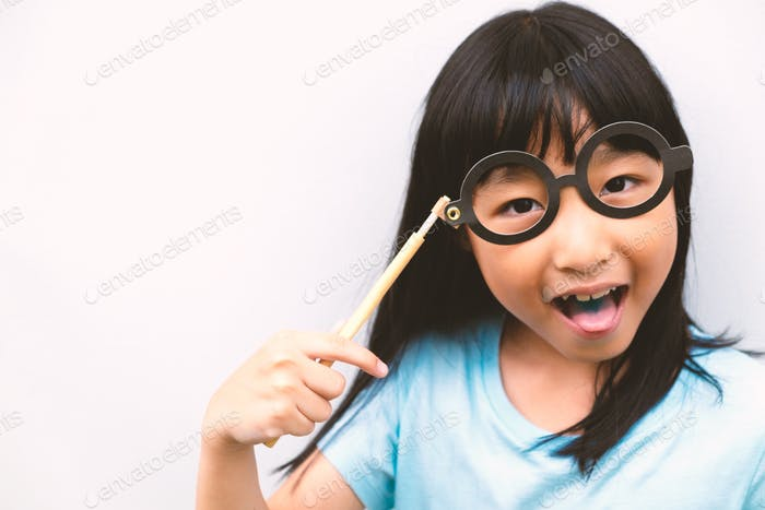 Headshot portrait of a Thai little girl putting party eyeglasses on her face isolated on white. She