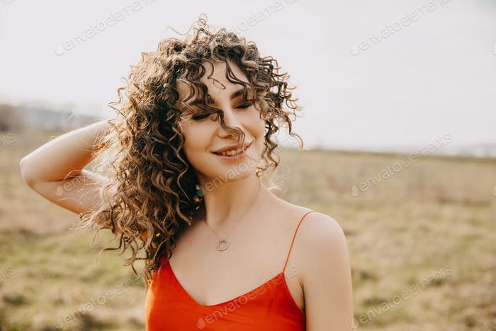 Portrait of a young woman with curly hair, smiling, outdoors.