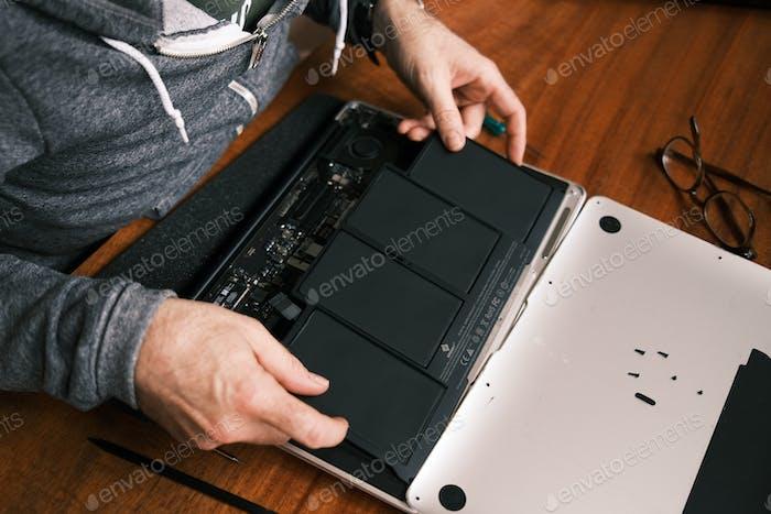 Proyecto de bricolaje: hombre arreglando su computadora en casa
